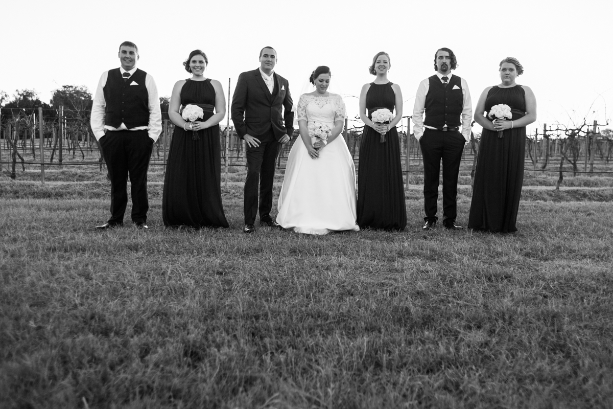 36_bridal party pose for photo in wine country vineyards
